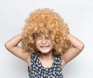 佩带一个白肤金发的假发和滑稽的表情亚洲人女孩 免版税库存图片