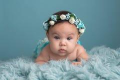 佩带一个花卉冠的女婴 免版税库存照片