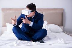佩带一个虚拟现实耳机的商人在卧室 图库摄影