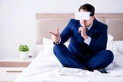 佩带一个虚拟现实耳机的商人在卧室 库存照片