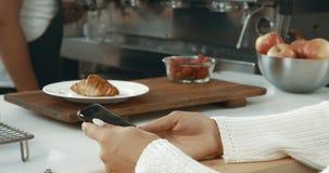 佩带一件白色毛线衣在顶楼样式面包店或与一个movile电话的可爱的少妇咖啡店 免版税库存照片