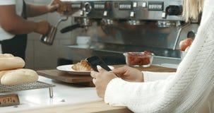 佩带一件白色毛线衣在顶楼样式面包店或与一个movile电话的可爱的少妇咖啡店 免版税库存图片