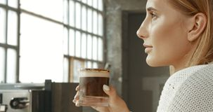 佩带一件白色毛线衣在顶楼样式面包店或与冰拿铁的可爱的少妇咖啡店 库存照片