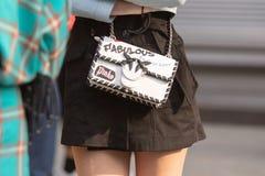 佩带一件黑超短裙和一个白色提包从倾左派的人的模型 图库摄影
