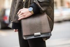佩带一块橄榄色的短夹克、金黄手表和一个棕色时髦提包,黑牛仔裤的一个时髦的女人的细节 免版税图库摄影