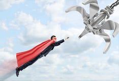 佩带一次红色超级英雄海角飞行的商人通过跟随一台机器人操作器的云彩 免版税库存图片