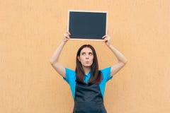 佩带一致的围裙的女性雇员拿着黑板标志 免版税库存照片