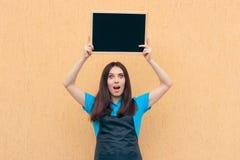 佩带一致的围裙的女性雇员拿着黑板标志 库存图片