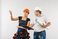 佩带一顶安全帽或盔甲和工友建造者妇女回顾的图纸的一个建筑师人 图库摄影