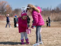 佩带与兔宝宝` s耳朵的两个可爱的白肤金发的白种人姐妹是在草甸参加复活节彩蛋狩猎 库存图片