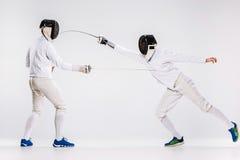 佩带两个的人操刀实践与剑的衣服反对灰色 免版税库存图片