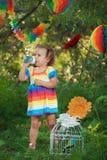 佩带五颜六色的礼服饮用水的逗人喜爱的小女孩 库存图片