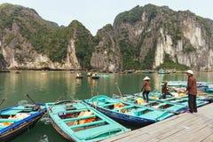 佩带亚洲圆锥形小船的划船男人和妇女帽子等待的游人停止在鲜绿色水 库存图片