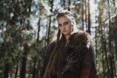 佩带传统战士的北欧海盗妇女在一个深神奇森林穿衣 免版税库存图片