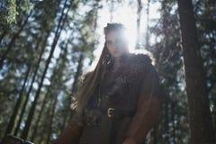 佩带传统战士的北欧海盗妇女在一个深神奇森林穿衣 库存图片