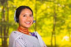 佩带传统安地斯山的披肩和红色项链的特写美丽的少妇,摆在为与耳机的照相机 库存图片