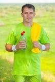 佩带体育的年轻人穿衣与黄色棉花毛巾holdin 免版税库存照片