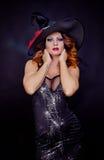 佩带作为巫婆的红发妇女为万圣夜 免版税库存照片