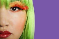 佩带假睫毛的少妇的播种的图象反对紫色背景 库存照片