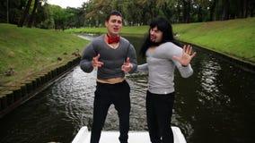 佩带假肌肉的两帅哥在小船填塞了服装跳舞并且唱歌 影视素材