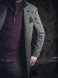 佩带偶然布料的男性模型摆在灰色背景 免版税图库摄影