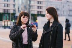 佩带偶然步行的两个时髦的年轻女朋友在城市附近和沟通 拿着太阳镜的一个女孩 库存图片
