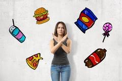 佩带偶然牛仔裤和T恤杉显示的年轻深色的女孩拒绝标志对在白色隔绝的不健康的便当快餐 免版税图库摄影
