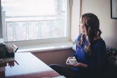 佩带偶然蓝色在餐馆caffe的Diwa天使神秘的夫人妇女礼服偏僻的开会与等候她的boyfreind hu的coffe杯子 免版税库存照片