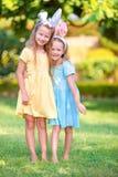 佩带兔宝宝耳朵的两个可爱的妹在复活节天户外 免版税库存照片