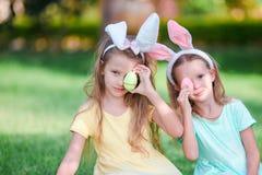 佩带兔宝宝耳朵的两个可爱的妹在复活节天户外 免版税库存图片
