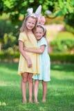 佩带兔宝宝耳朵的两个可爱的妹在复活节天户外 库存图片