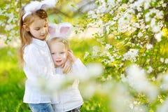 佩带兔宝宝耳朵的两个可爱的妹在春天庭院里在复活节天 库存图片
