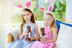 佩带兔宝宝耳朵的两个逗人喜爱的妹吃巧克力复活节兔子 演奏在复活节的孩子蛋狩猎 库存照片