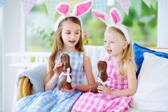 佩带兔宝宝耳朵的两个逗人喜爱的妹吃巧克力复活节兔子 免版税库存图片