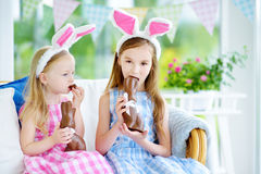 佩带兔宝宝耳朵的两个逗人喜爱的妹吃巧克力复活节兔子 免版税图库摄影