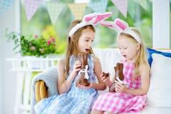 佩带兔宝宝耳朵的两个逗人喜爱的妹吃巧克力复活节兔子 图库摄影