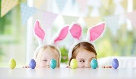 佩带兔宝宝耳朵的两个逗人喜爱的妹演奏鸡蛋在复活节寻找 库存照片