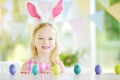 佩带兔宝宝耳朵的两个逗人喜爱的妹演奏鸡蛋在复活节寻找 免版税库存照片