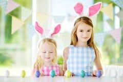 佩带兔宝宝耳朵的两个逗人喜爱的妹演奏鸡蛋在复活节寻找 免版税库存图片