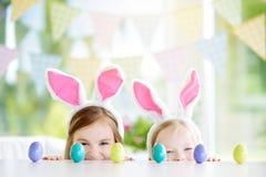 佩带兔宝宝耳朵的两个逗人喜爱的妹演奏鸡蛋在复活节寻找 免版税图库摄影