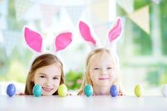 佩带兔宝宝耳朵的两个逗人喜爱的妹演奏鸡蛋在复活节寻找 库存图片