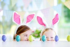 佩带兔宝宝耳朵的两个逗人喜爱的妹演奏鸡蛋在复活节寻找 图库摄影