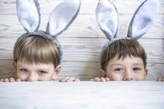 佩带兔宝宝耳朵的两个逗人喜爱的弟弟演奏鸡蛋在复活节寻找 可爱的孩子在家庆祝复活节 库存照片
