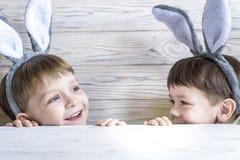 佩带兔宝宝耳朵的两个逗人喜爱的弟弟演奏鸡蛋在复活节寻找 可爱的孩子在家庆祝复活节 免版税库存图片