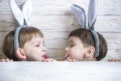 佩带兔宝宝耳朵的两个逗人喜爱的弟弟演奏鸡蛋在复活节寻找 可爱的孩子在家庆祝复活节 免版税库存照片