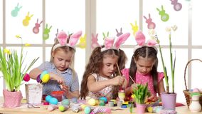 佩带兔宝宝耳朵的愉快的孩子绘鸡蛋在复活节天 股票录像