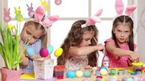 佩带兔宝宝耳朵的愉快的孩子绘鸡蛋在复活节天 股票视频