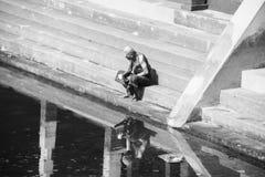 佩带典型的长袍选址的老人在Sree Padmanabhaswamy寺庙水池在期间在特里凡德琅,印度 黑色白色 免版税库存图片