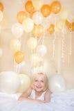 佩带冠的一个女孩由在ba的气球围拢 免版税库存图片