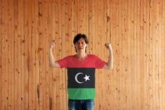 佩带利比亚衬衣的旗子颜色和站立与在木墙壁背景的被举的拳头的人 免版税库存图片
